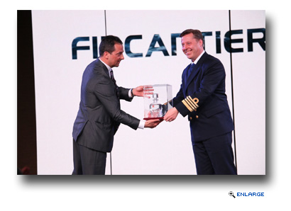 Antonio Quintano, shipyard director for Italian shipbuilder Fincantieri (left), presents Captain Emiel de Vries of Holland America Line's Koningsdam, with the bottle containing the first water touched by the new ship, which made its debut in Rotterdam, the Netherlands in May 2016. The bottle is kept on the ship as a sign of good luck.