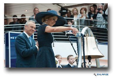 Queen M�xima performs the ceremonial honors of blessing the ship�s bell in the Lido pool area by pouring a glass of champagne over the bell